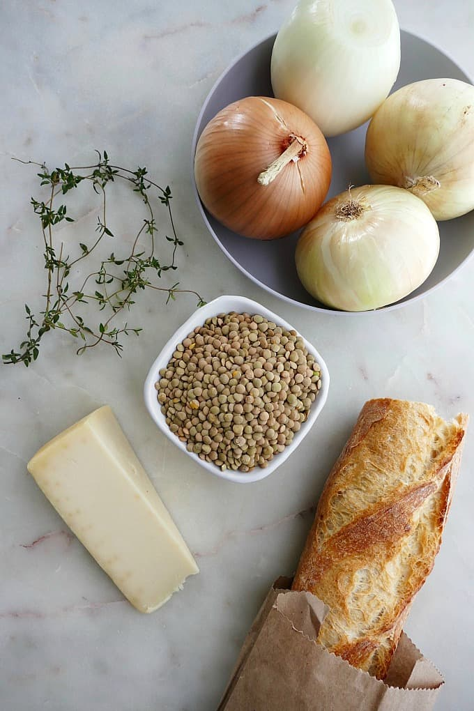 ingredients for french onion soup with lentils on a white countertop