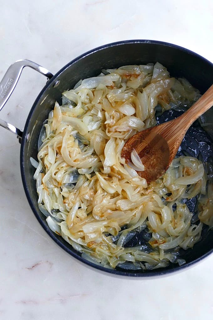 sauteed sweet onions in a black pot with a wooden spoon