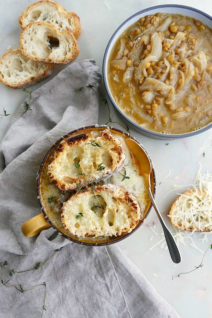 vegetarian french onion soup with lentils in a small bowl next to a larger bowl