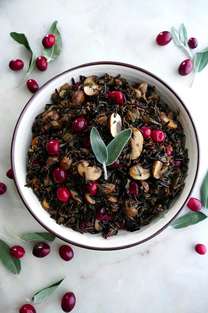 wild rice pilaf with mushrooms and cranberries in a white bowl topped with sage