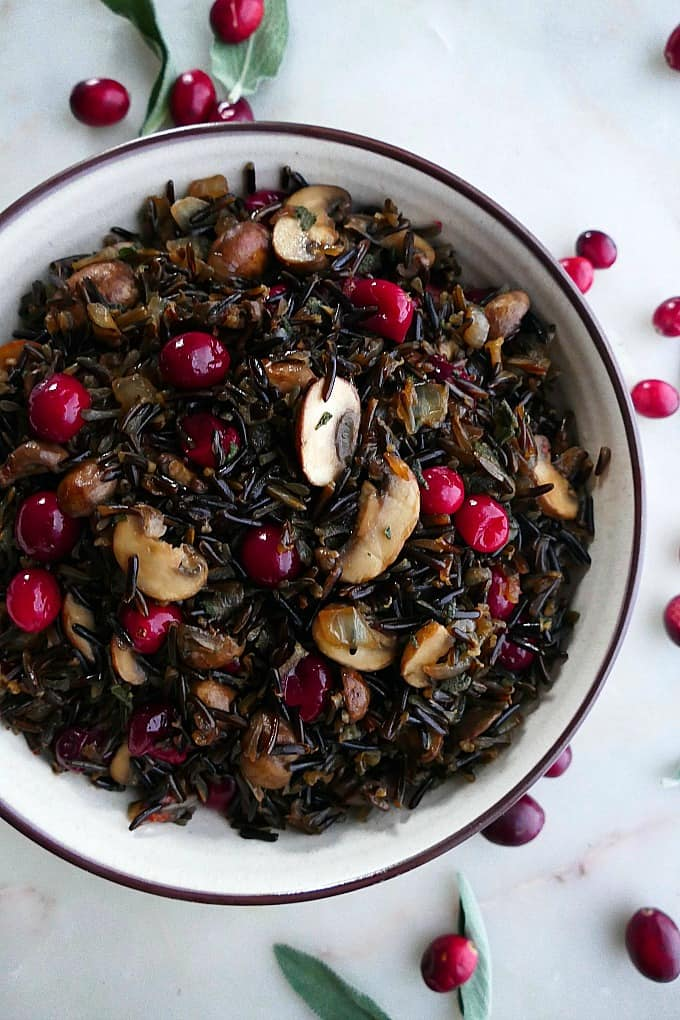 close up of wild rice pilaf with mushrooms and cranberries in a white bowl