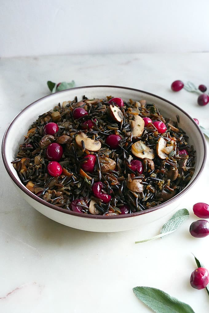 side view of wild rice pilaf in a white bowl with sage and cranberries on the side