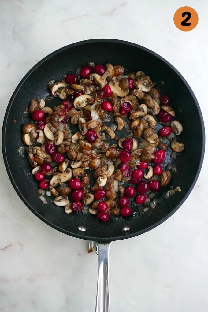 sauteed mushrooms, onions, and cranberries in a black skillet on a white countertop