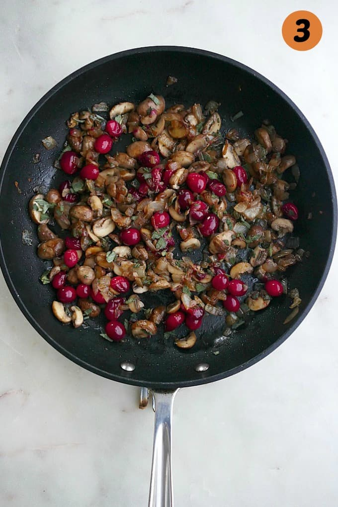 mushrooms, onions, cranberries, sage in a black skillet on a white countertop