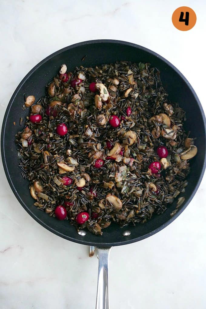 sauteed mushrooms, cranberries, and wild rice in a black skillet on a counter