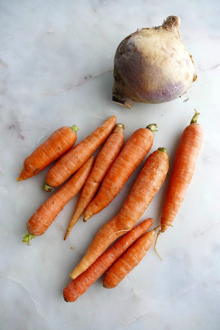 11 carrots and 1 rutabaga next to each other on a white countertop
