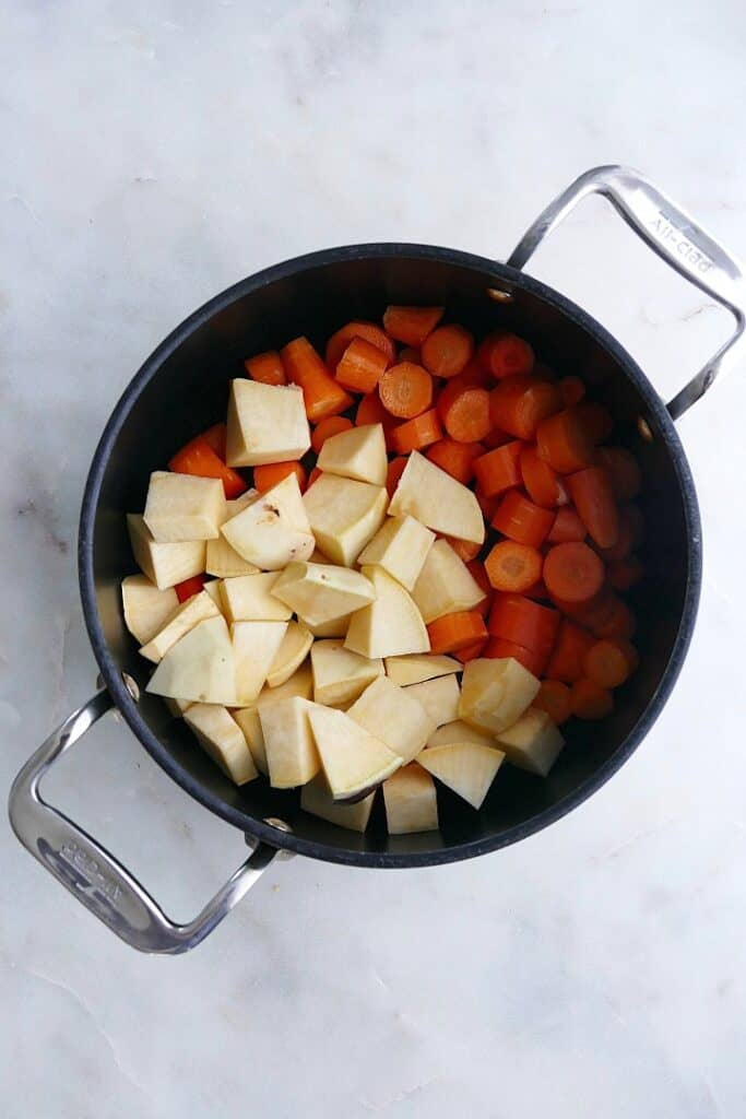 diced rutabaga and carrots in a large black pot on a counter
