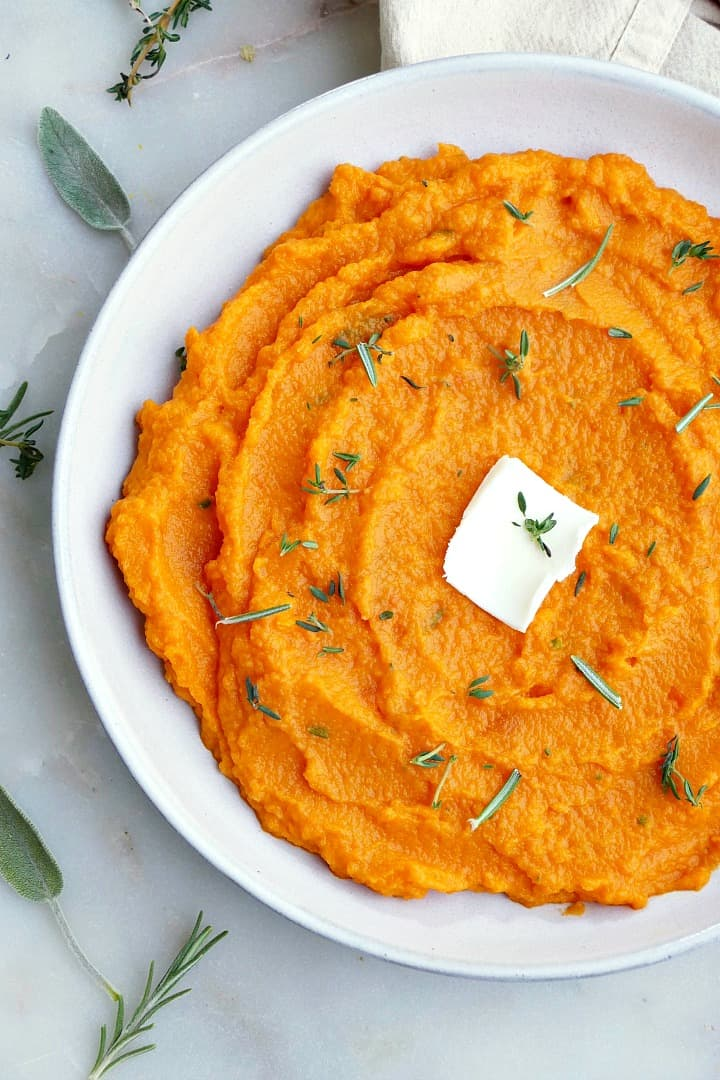 close up of carrot and swede mash on a white plate with butter and herbs