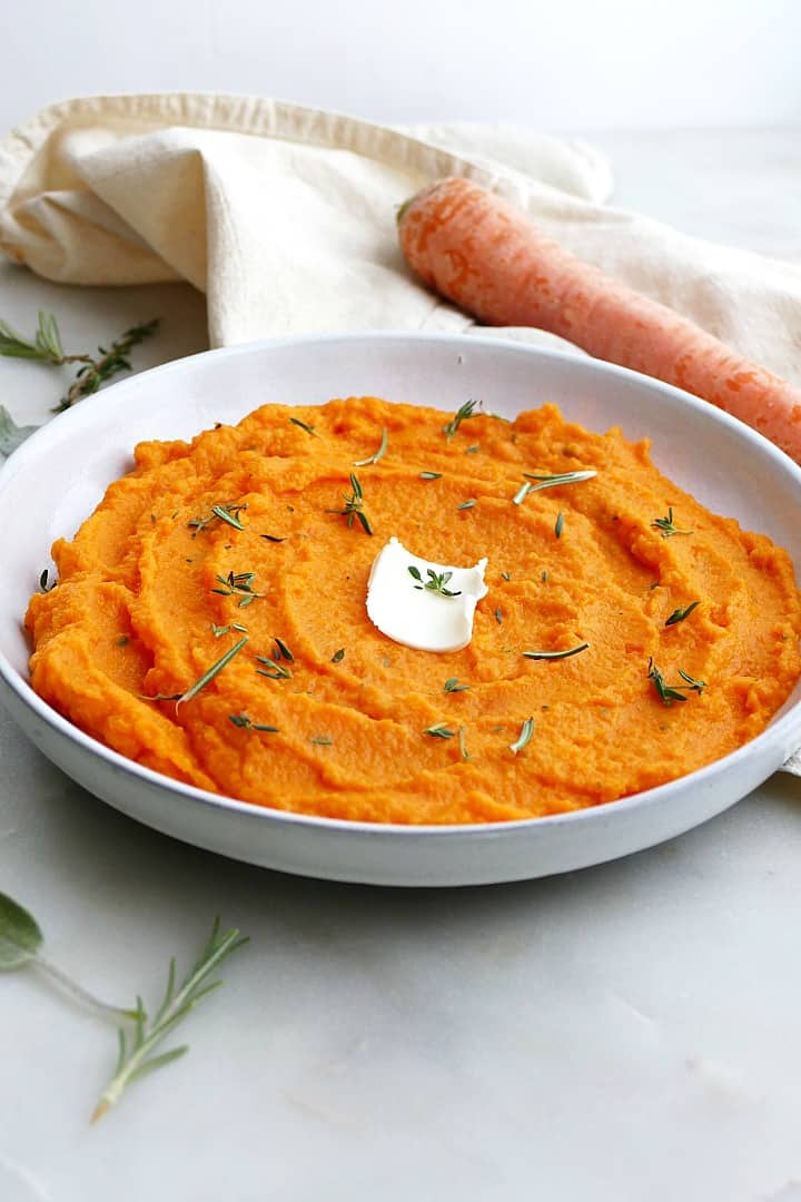side view of carrot and swede mash on a white plate with butter and herbs