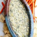 spinach artichoke dip with greek yogurt in a blue and brown dish surrounded by carrots and chips