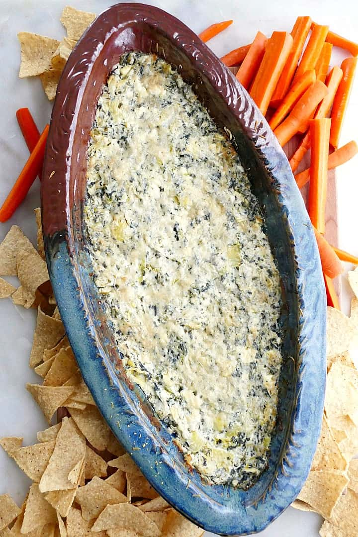 spinach artichoke dip with greek yogurt in a blue brown dish surrounded by carrots and chips