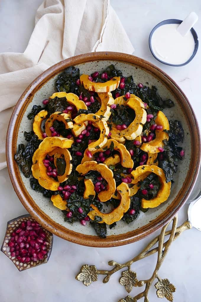 roasted delicata squash and kale without dressing in a large bowl on counter