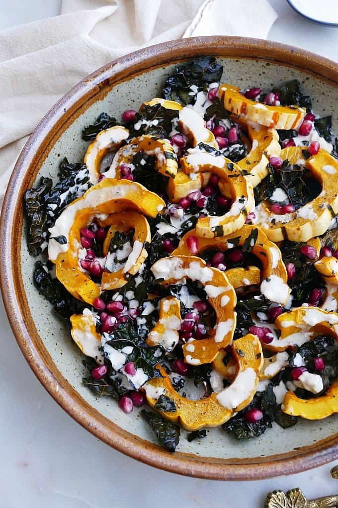 close up of roasted delicata squash and kale in a bowl with pomegranate seeds and dressing