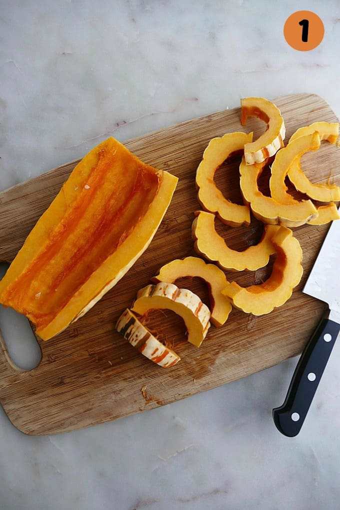 sliced delicata squash on a bamboo cutting board with a knife