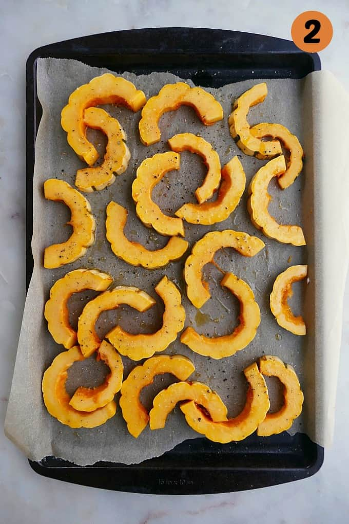 delicata squash cut into half-moons on a baking sheet lined with parchment paper