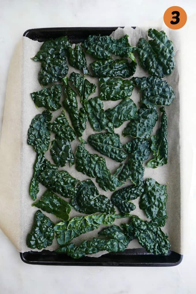 lacinato kale leaves on a baking sheet lined with parchment paper