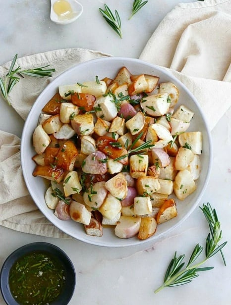 close up of roasted turnips and pears on white plate on top of a yellow napkin
