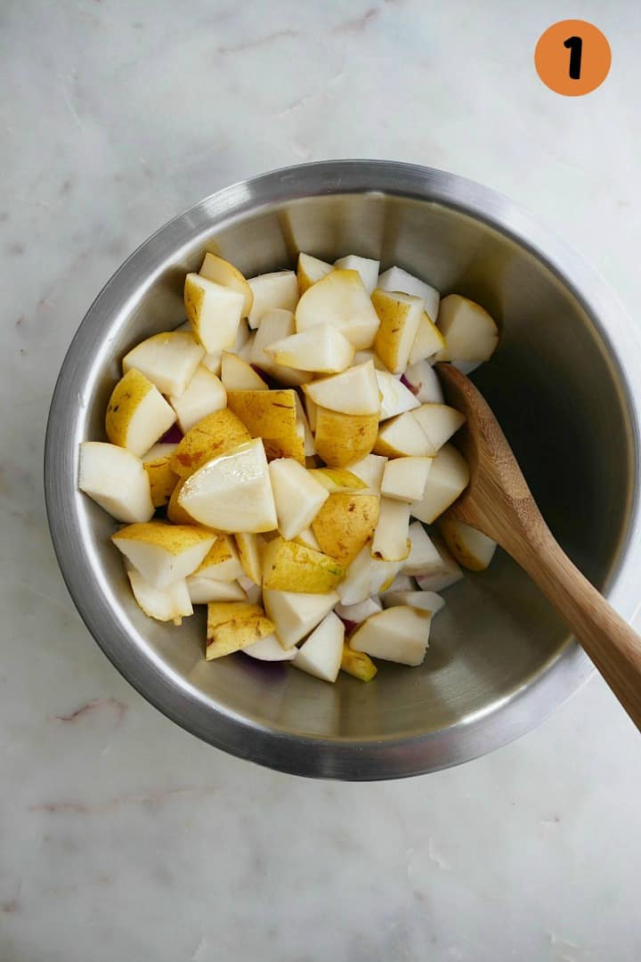 mixing bowl with diced pears and turnips with a wooden spoon