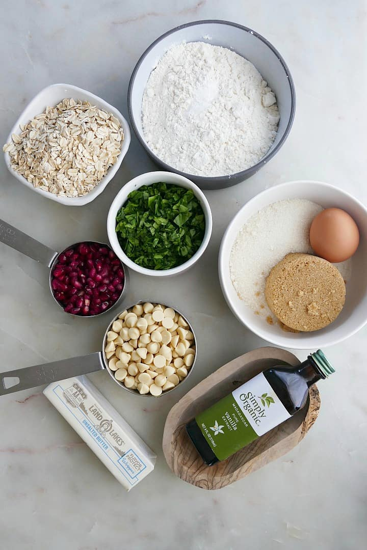 ingredients for white chocolate chip spinach cookies in bowls on a white counter