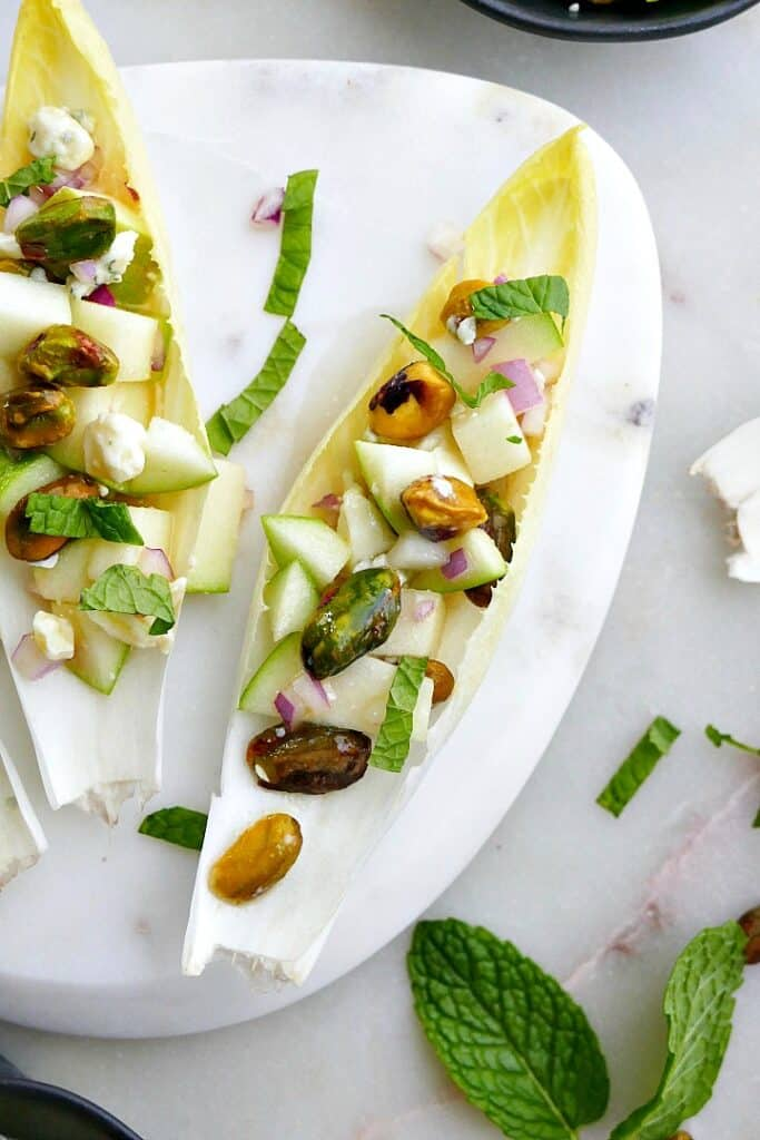 close up of stuffed belgian endive with apple, blue cheese, pistachios, and mint