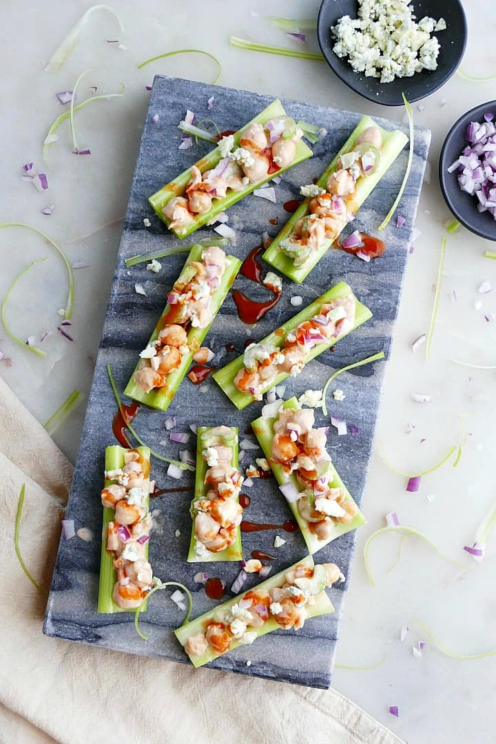 8 buffalo chickpea salad stuffed celery sticks next to small bowls
