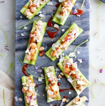 8 buffalo chickpea salad stuffed celery sticks on a blue marble board on a white counter