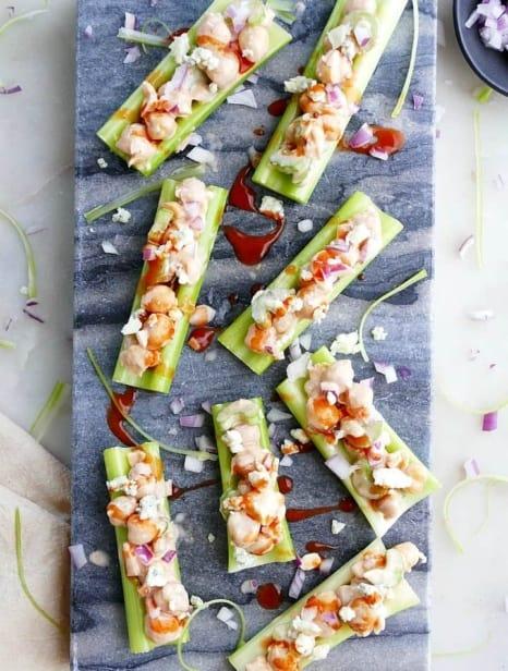 8 buffalo chickpea salad stuffed celery sticks on a blue marble board on a white counter