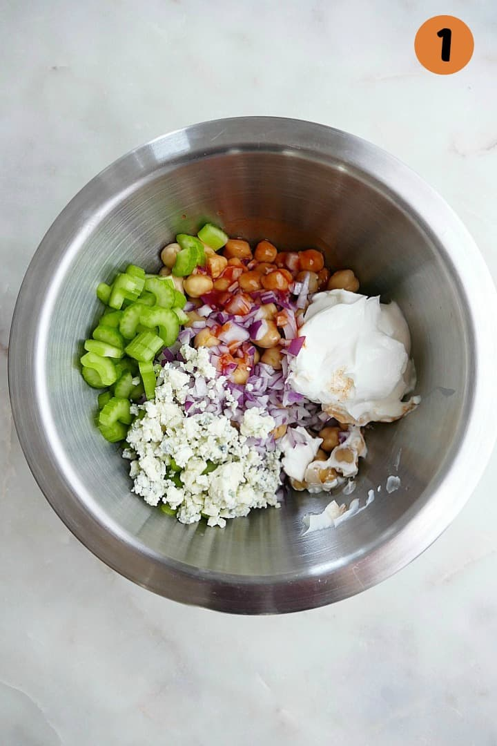 ingredients for buffalo chickpea salad in a metal mixing bowl on a counter