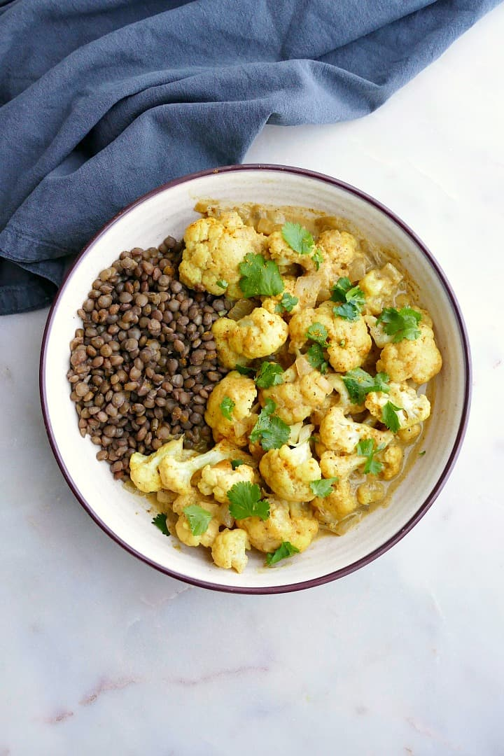 cauliflower curry with lentils and cilantro in a white bowl on a white counter