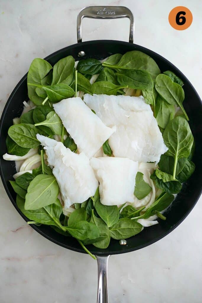 cod fillets on top of spinach and fennel in coconut milk in a black skillet