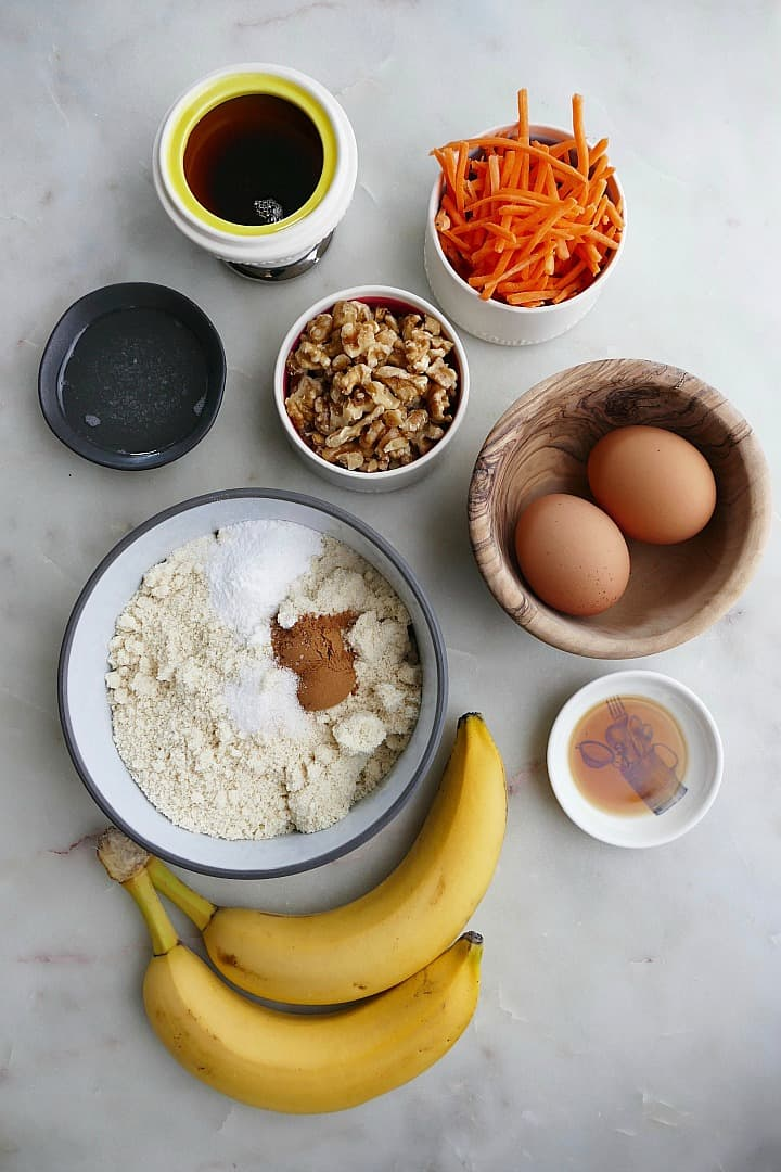 banana, eggs, flour, carrots, walnut, vanilla, and syrup on a white counter