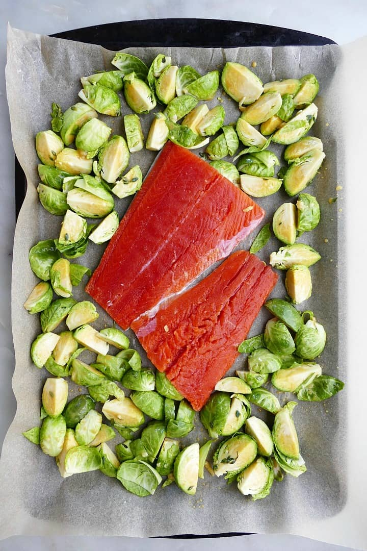 raw salmon and brussels sprouts on a baking sheet lined with parchment paper