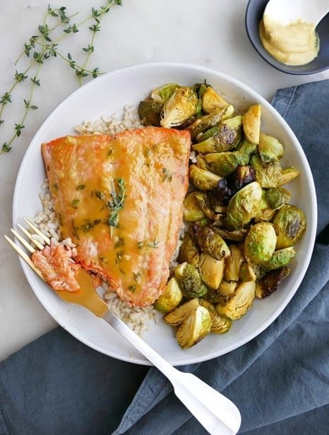 maple mustard salmon and brussels sprouts on a white plate with a gold fork
