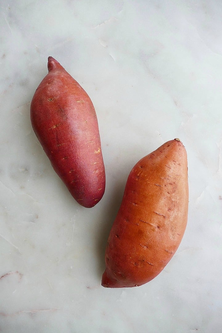 two large sweet potatoes on a white marble counter top
