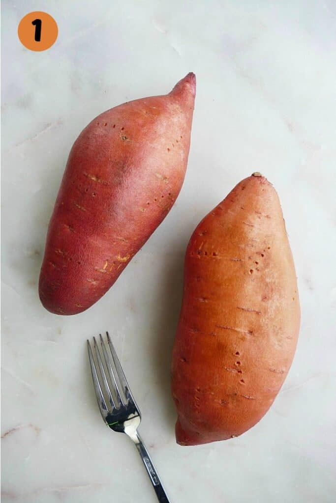 two sweet potatoes on a white countertop with fork holes and a fork next to them