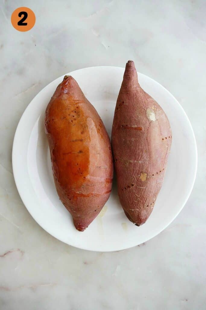 two microwave sweet potatoes on a white plate on a white counter