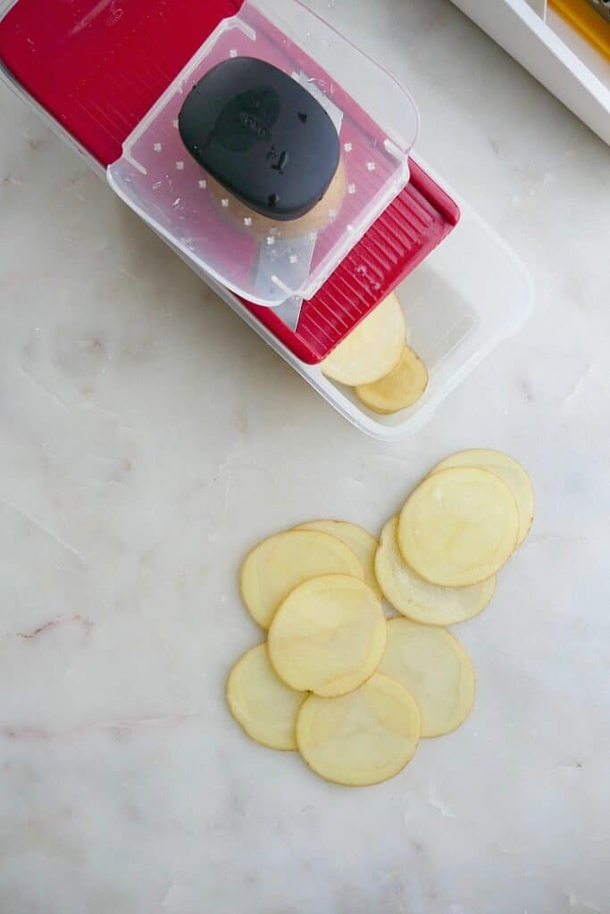 sliced white potatoes next to a red mandoline on a counter