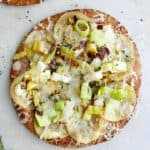 potato leek pizza on pita on a white counter with rosemary