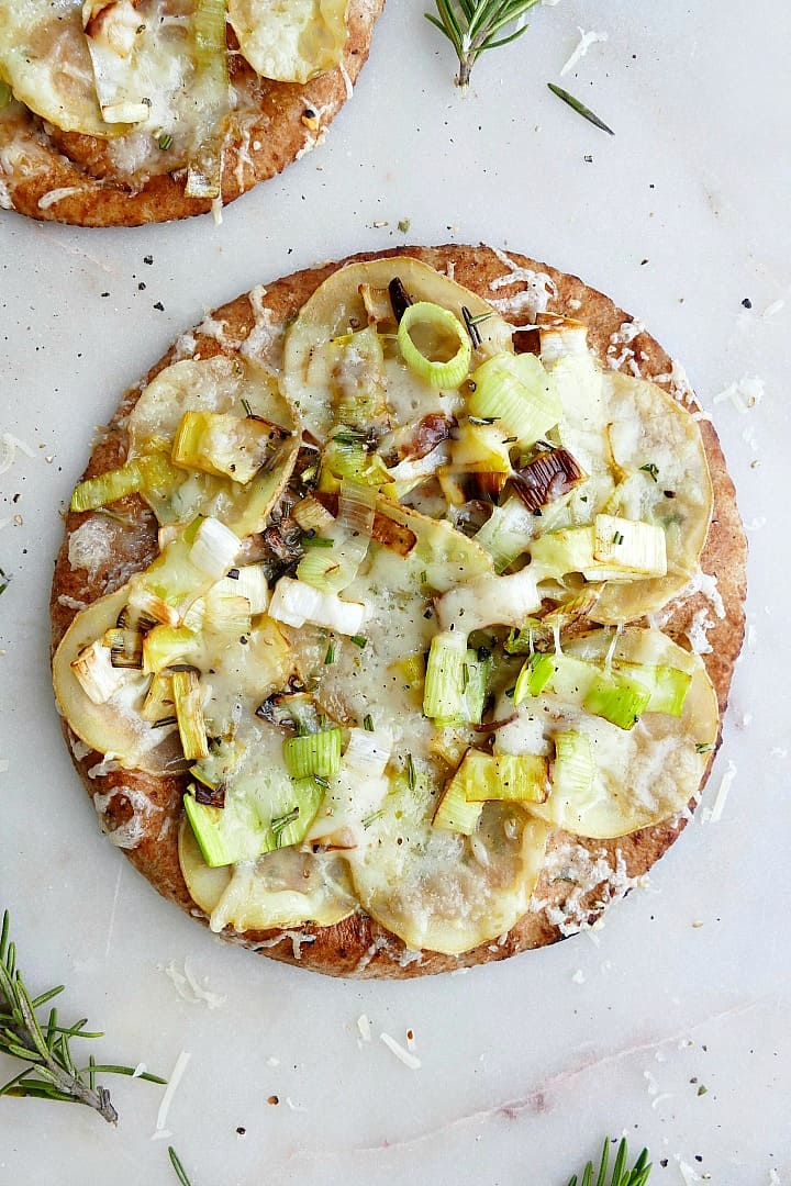potato leek pizza on pita on a white counter with rosemary