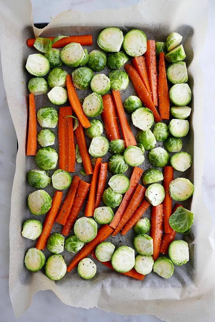 sliced brussels sprouts and carrots on a baking sheet lined with parchment paper