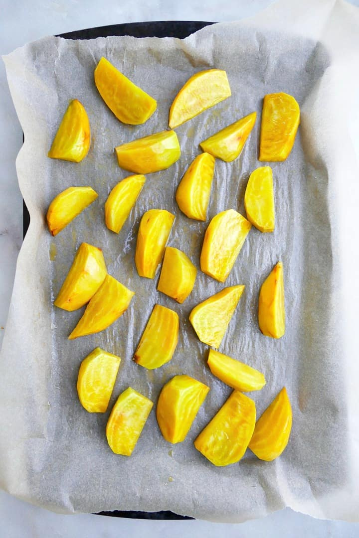 sliced golden beets in oil on a baking sheet lined with parchment paper