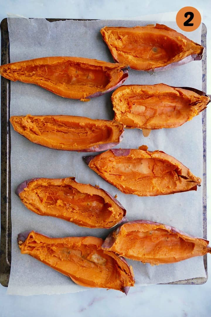 8 sweet potato jackets with their flesh scooped out on a baking sheet lined with parchment