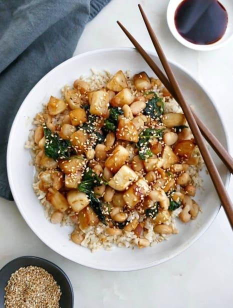 turnip stir fry on a white plate with brown chopsticks next to a blue napkin