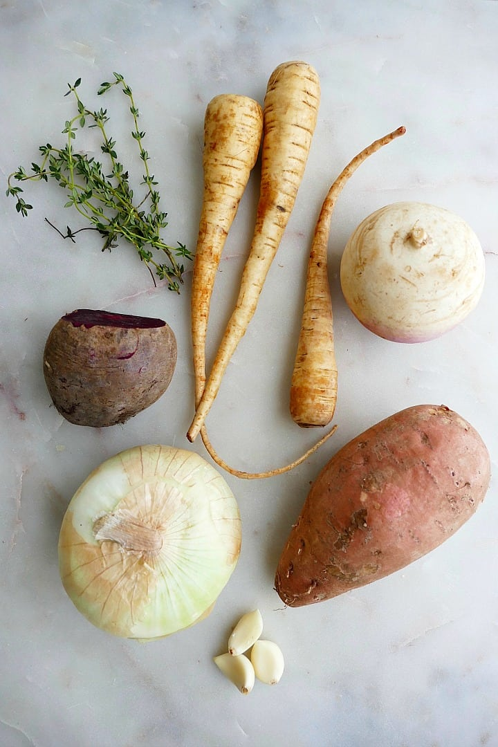 thyme, beet, parsnips, onion, sweet potato, garlic, and turnip on a counter
