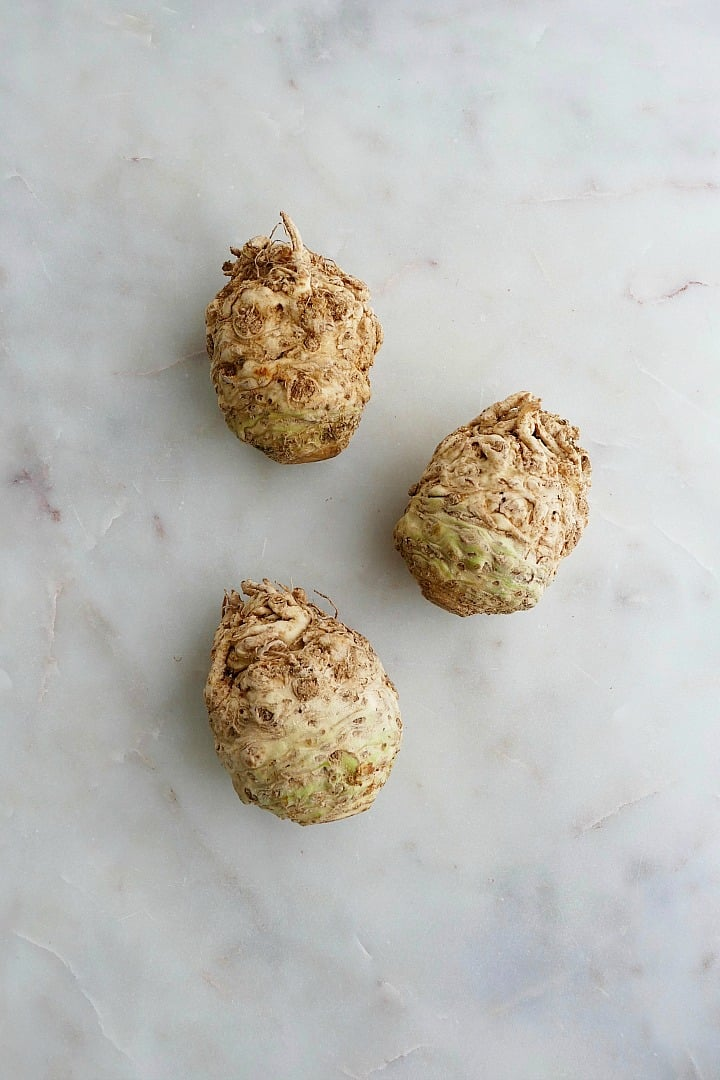 three knobs of celery root next to each other on a white counter