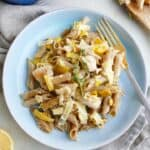 blue plate with chicken and leek pasta bake and a gold fork