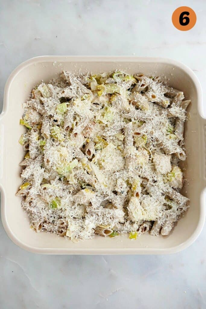 whole wheat penne pasta topped with chickens, leek sauce, and cheese in an 8x8 baking dish