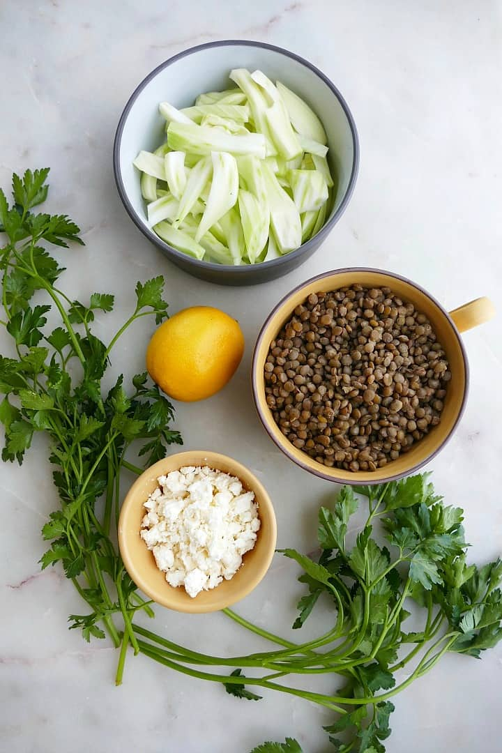 parsley, feta, lemon, lentils, and fennel in bowls on a counter