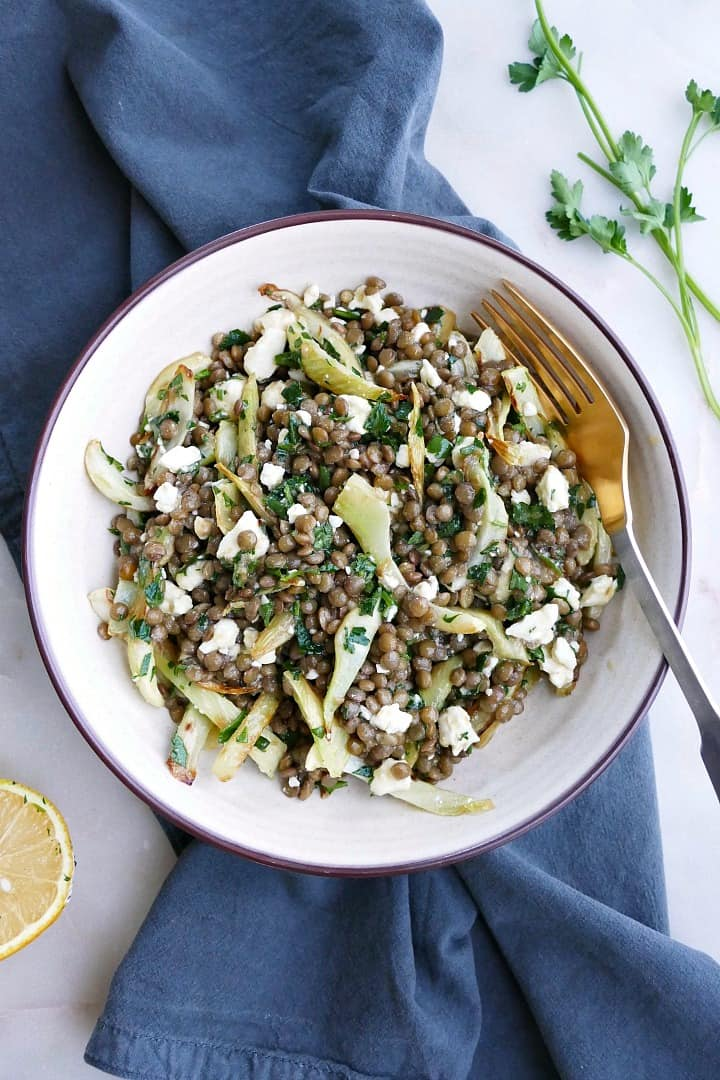 a white bowl with fennel and lentil salad on top of a blue napkin