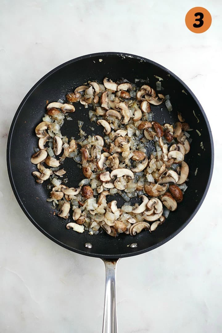 diced mushrooms and onion cooking a black skillet on a white counter with the number 3 in the top